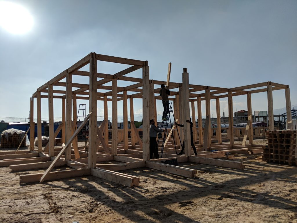 Partners assembling the modular wood frame structure on site.