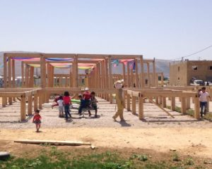 The modular wooden play structure, pictured with children playing.